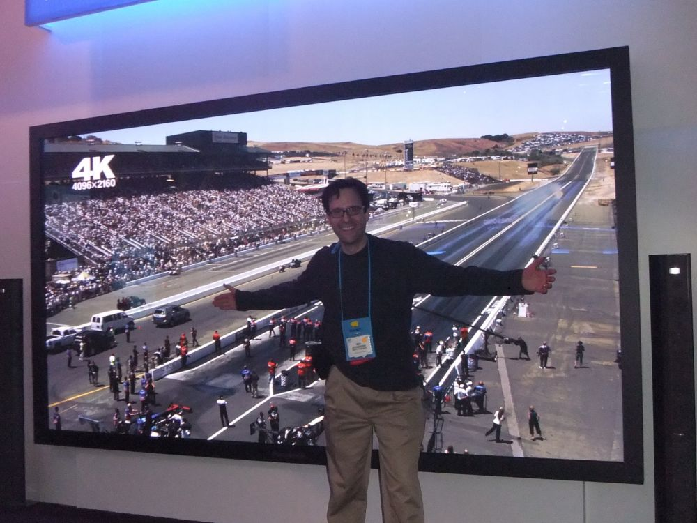 "Neil Schneider, CEO of MTBS, in front of 150"" Panasonic 3D Ready plasma."
